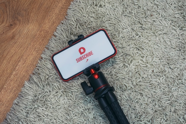 Subscribe to the internet channel on the smartphone display on a flexible tripod against the background of the carpet.