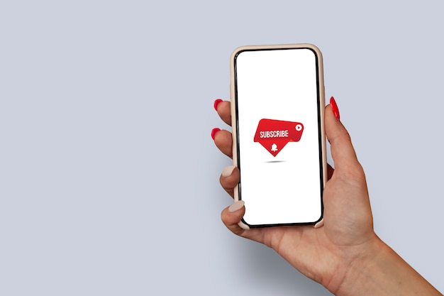 스마트폰 디스플레이에서 인터넷 채널을 구독하세요. 손톱이 아름다운 소녀는 무료 wifi 아이콘이 있는 스마트폰 클로즈업을 들고 있습니다.