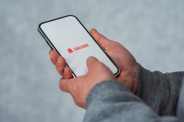 Подпишитесь на интернет-канал на дисплее смартфона. мужчина держит смартфон крупным планом со значком.