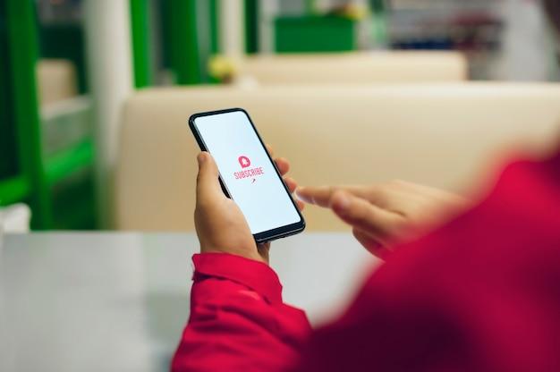 ビデオチャンネルを購読します。白いスマートフォン画面の行動を促すフレーズのアイコン。