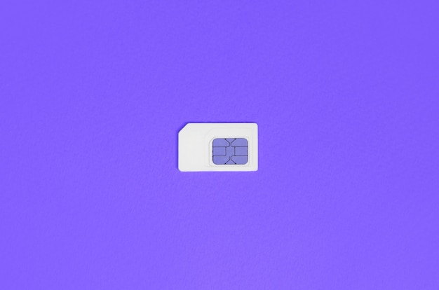 Subscriber identity module. white sim card on violet