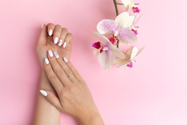 난초 꽃과 분홍색 배경에 흰색 손톱으로 아름 다운 젊은 여자의 손의 미묘한 손가락. 스파, 핸드 케어 개념. 복사 공간 배너. 매니큐어와 젤 광택을 가진 여성 손