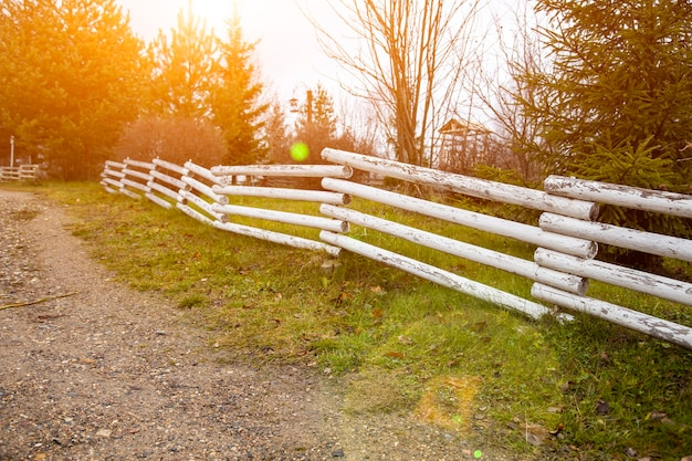 Suburban wooden fence along the country road sunny day