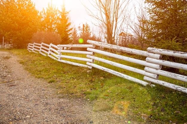 田舎道に沿った郊外の木製柵晴れた日