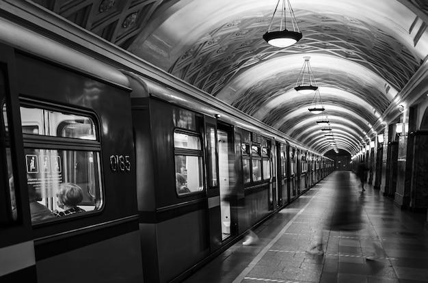 動く人々のシルエットの地下鉄の車とプラットフォーム