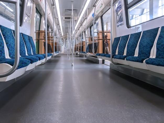 Интерьер вагона метро с красочными сиденьями без пассажиров
