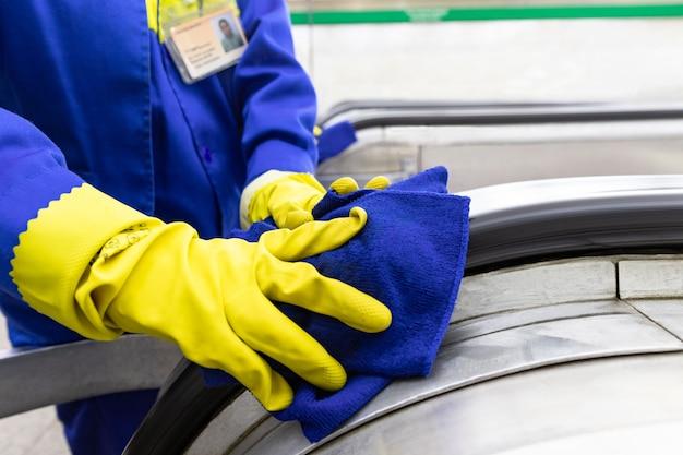 地下鉄のスタッフがエスカレーターの手すりを掃除する