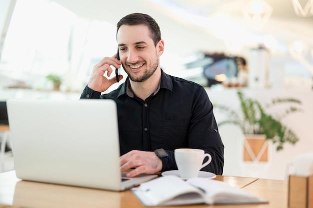 成功したリモート男性労働者。電話に満足している若いフリーランサーの男。背景のコーヒーショップ。コーヒーショップで働く男性のフリーランサープログラマー。彼はクライアントと喜んで話をします