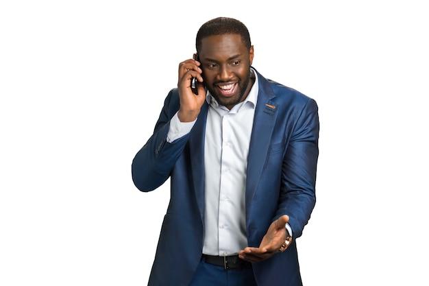 Успешный улыбающийся бизнесмен с мобильным телефоном. взволнованный директор компании слышит по мобильному телефону позитивные новости