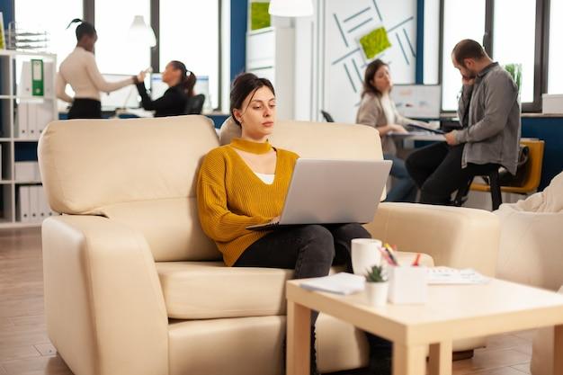 Успешная деловая женщина, работающая на ноутбуке над запуском проекта, сидя на уютном диване