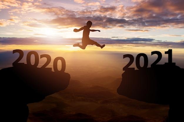 Успешная новогодняя концепция 2021 года. силуэт человека прыгает между 2020 годом на фоне холмов и неба на закате