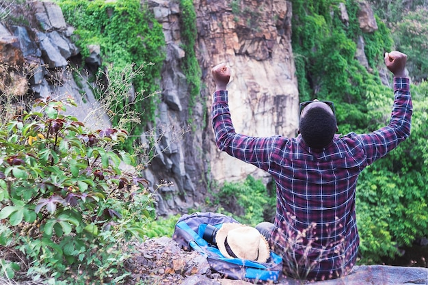 Успешный африканский путешественник сидит на вершине горы с рюкзаком и шляпой
