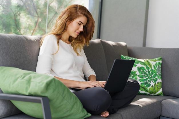 성공 및 프리랜서 작업. 그녀의 빌라의 아늑한 방에 있는 소파에 앉아 노트북 작업을 하는 웃고 있는 비즈니스 여성의 전체 길이 보기. 스톡 사진