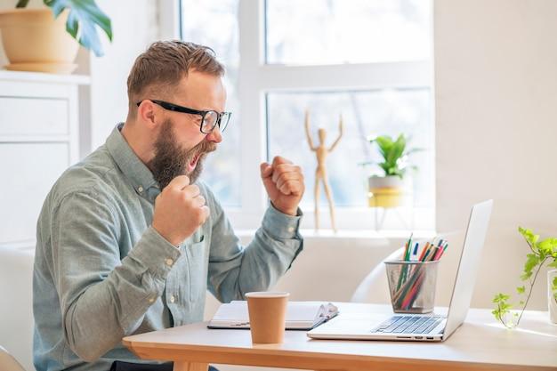 Концепция успеха и достижения цели. счастливый бизнесмен чувствовать волнение крик поднимая кулаки, глядя на ноутбук достижения жизненной цели, празднование успеха в бизнесе отличный результат сделать жест победителя