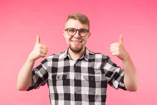 Концепция успеха и хорошего жеста - счастливый забавный человек показывает палец вверх на розовой поверхности