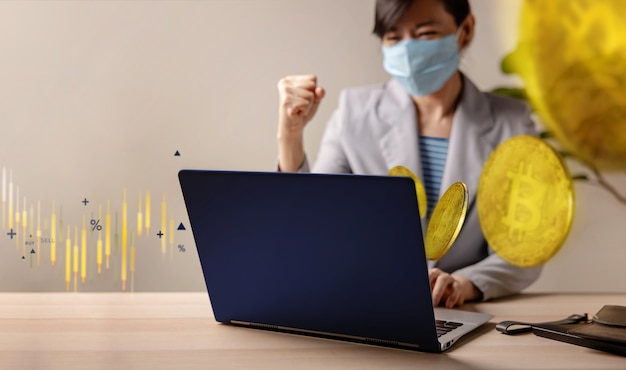 Success in blockchain economic investment during coronavirus crisis concept. cheerful young woman wearing medical mask while using computer laptop to buy and sell bitcoin via cryptocurrency exchange.