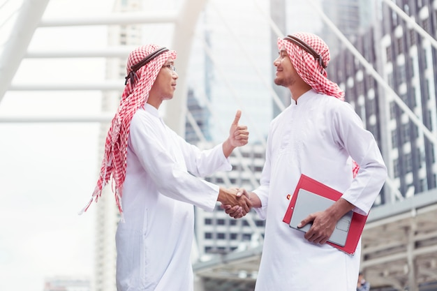 Success business deal, arab are shaking hand in city.