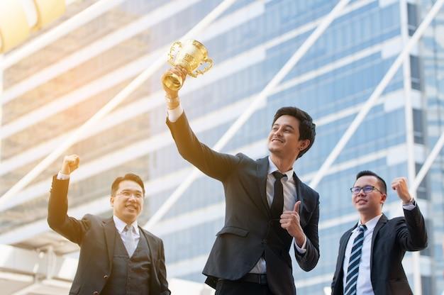 ゴールデントロフィーカップを持っている成功のビジネスマン