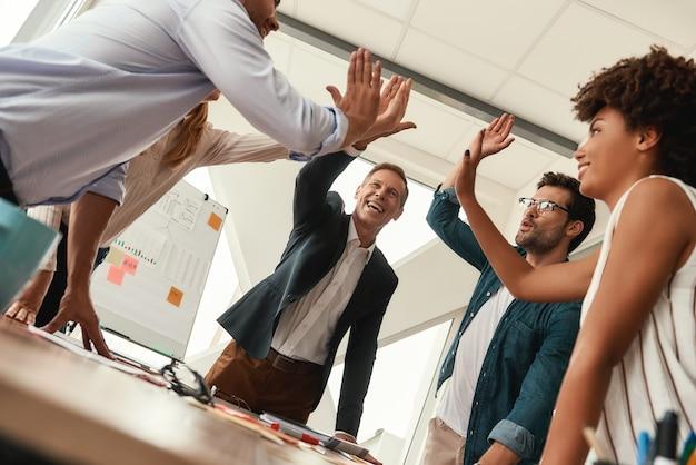 성공 비즈니스 사람들은 현대 사무실에서 함께 일하는 동안 서로 하이파이브를 하고 웃고 있습니다. 팀워크