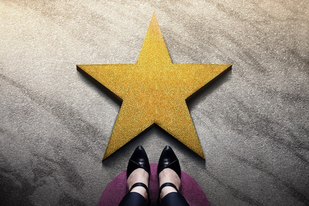 Success in business or personal talent concept. top view of business woman in working shoes standing in front of a golden star