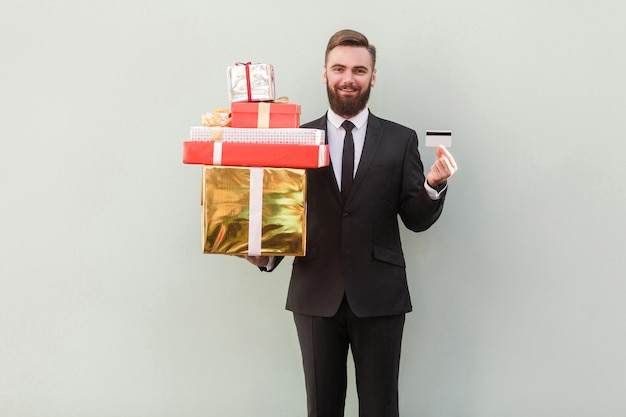 Зубастая улыбка бизнесмена успеха, держащая коробку и кредитную карту