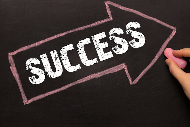 Успех - классная доска со стрелкой на черном фоне