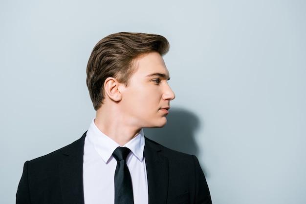 成功のコンセプト。コピースペースの隣の真っ青なスペースに立っている、フォーマルな服装の若いハンサムな男性の横顔写真