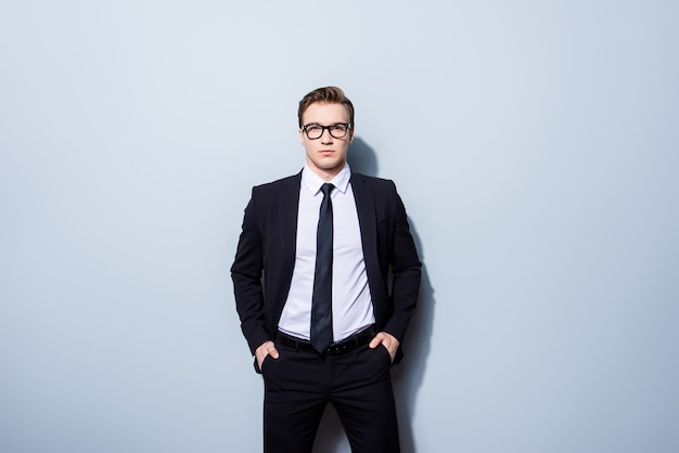 Концепция успеха. стильный молодой юрист, стоящий на чистом пространстве, в черном костюме и галстуке, выглядит таким классным и ботанистым!