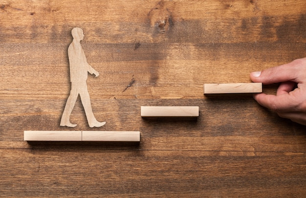Success concept with wooden businessman climbing wooden block stairs
