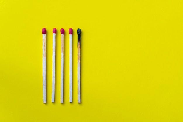 Success, defeat, achievement. the concept of happiness. matches on a yellow background. burnt dark match among normal matches. burning match fire to its neighbors, a metaphor for ideas and inspiration