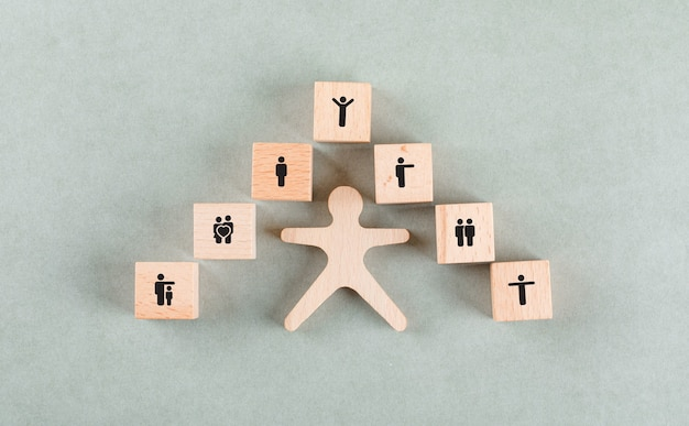 Success employee concept with wooden human, blocks with icons.