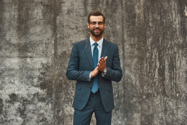 Success in everything confident and happy bearded businessman in full suit rubbing his palms and
