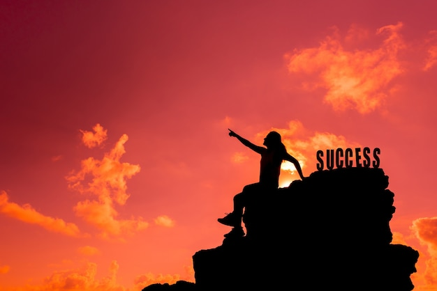 Success and failure concept. silhouette sporty woman on the cliff. with copy space on skyfor text