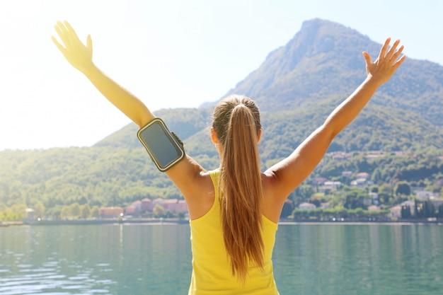 Концепция женщины фитнеса успеха с браслетом спорта для телефона. выигрышная концепция бегуна-спортсменки, аплодирующего с поднятыми руками для достижения цели в потере веса или жизни.