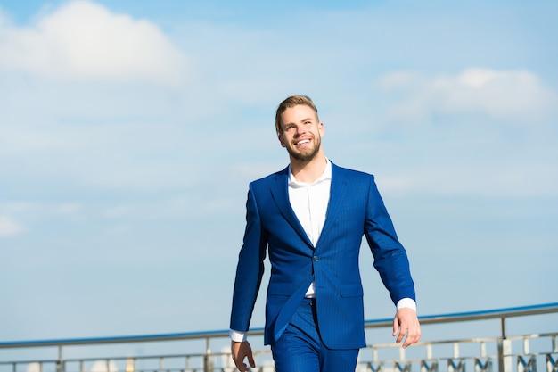彼の2番目の名前を成功させます。スーツを着たビジネスマンの成功した起業家は、屋外の晴れた日の空の背景を歩きます。自信を持って手入れの行き届いた男性は自由を楽しんでいます。運と成功のコンセプト。優れていると感じます。