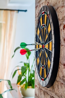 Success hitting target aim goal achievement concept background - darts in bull's eye close up. red, green darts arrows in the target center business goal concept