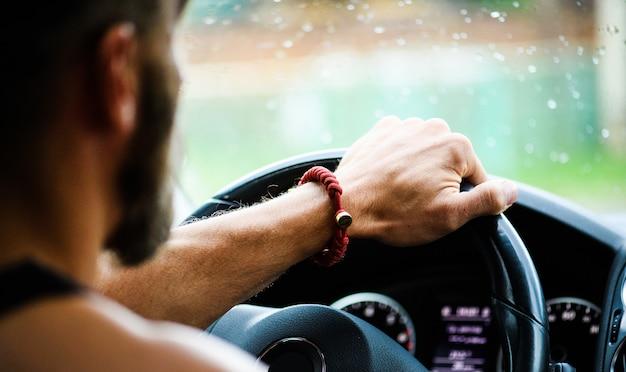 動きの成功。車を運転するハンサムな男。スピードメーターとタコメーターを含む車のインテリア
