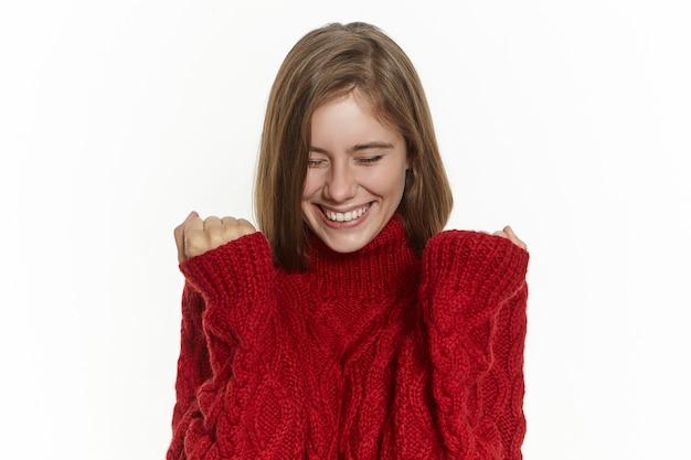 Концепция успеха, радости и счастья. счастливая возбужденная молодая женщина в стильном теплом свитере позирует изолированно, сжав кулаки и широко улыбаясь, радуясь хорошим новостям, воплощая в жизнь свою мечту