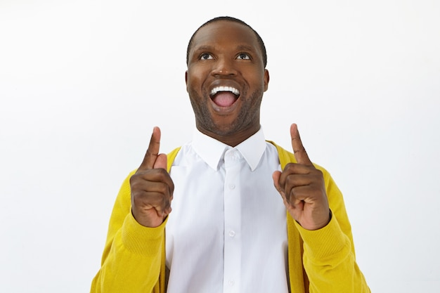 성공, 기쁨과 승리 개념. 두 검지 손가락을 위쪽으로 가리키는 흥분과 완전한 불신을 표현하고 입을 벌리고 올려 보는 감정적 인 재미 아프리카 남성의 스튜디오 샷