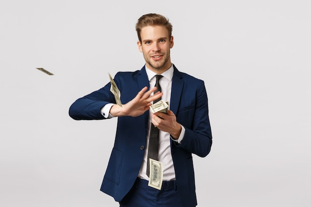 Success, money and finance concept. handsome confident, blond bearded businessman in suit, holding cash and throwing money in air with pleased, satisfied expression, wasting dollars