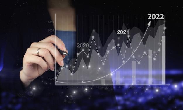성공 새 해 개념입니다. 비즈니스 관리, 영감 개념 아이디어입니다. 디지털 그래픽 펜을 들고 디지털 홀로그램 성장 그래프 차트를 그리는 손은 도시의 어두운 흐릿한 배경에 표시됩니다.