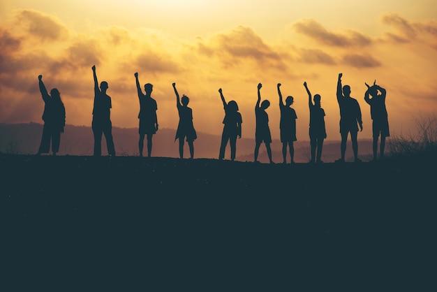 실루엣 일몰 배경에 팀워크 협업 및 자유의 성공. 사업 개념