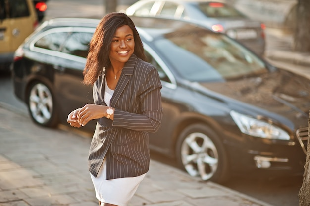 Success stylish woman in jacket against car.