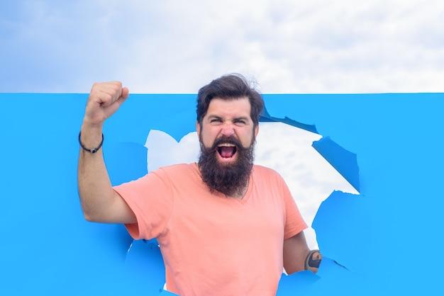 成功した成功した男は破れた紙の穴の男から覗く紙のひげを生やした男の穴を通して見る