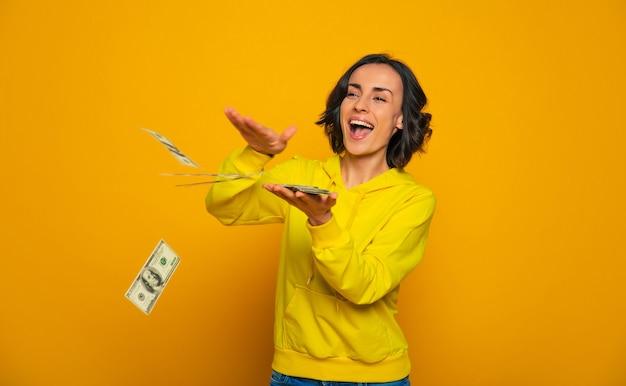 Успех! успешная молодая женщина в желтой толстовке с капюшоном, смеясь и бросая деньги.