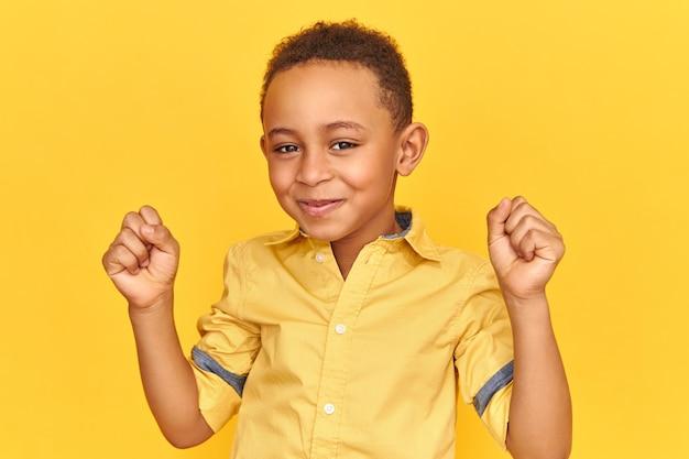 成功、勝利、喜びと幸福の概念。愛らしいかわいい興奮した小さなアフロアメリカンの男の子は、恍惚とした表情を大喜びし、笑顔で、拳を握りしめ、良い前向きなニュースを受け取りました
