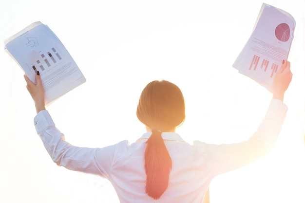Success and triumph of a young business woman with papers.