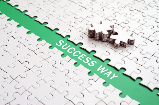 Success way. the green path is laid on the platform of a white folded jigsaw puzzle