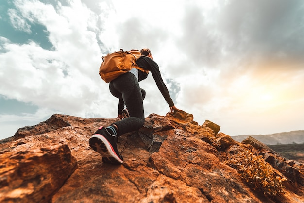 성공 여성 등산객 일출 산 피크에 하이킹-배낭에 젊은 여자는 산 위로 상승. 발견 여행 목적지 개념