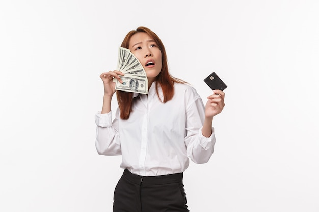 Success, women and career concept. satisfied pleased and boastful young asian female enjoying being rich, holding credit card and brush cheeks with dollars, have lots money,